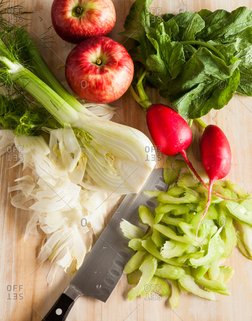 Fresh vegetables and apples on cutting board