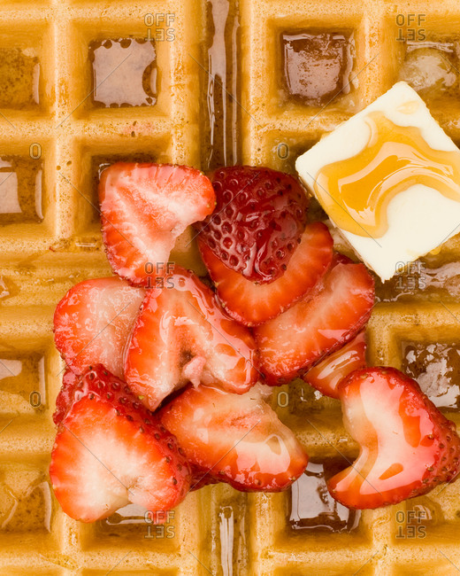 Close-up of waffles with strawberries and butter