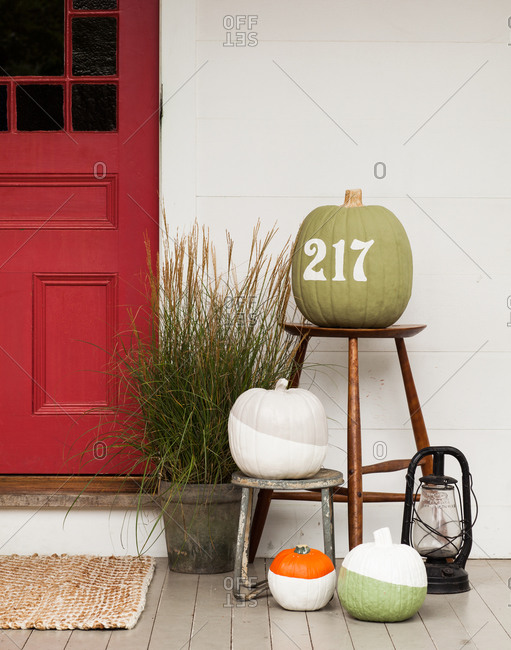 Painted pumpkins on wooden stools and a lantern next to entrance
