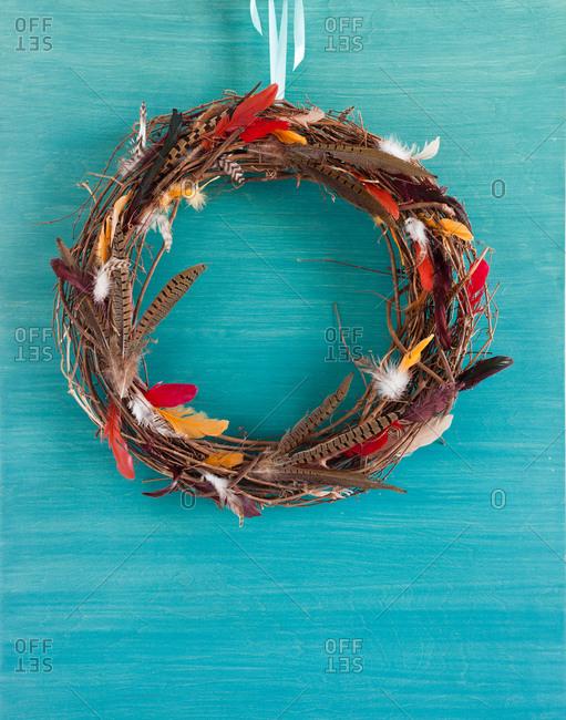 Bird nest wreath hanging over blue surface
