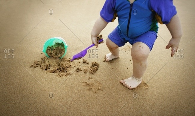 little kid plays in the sand