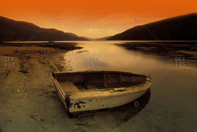 Row Boat At Water\'s Edge Against Sunset Backdrop