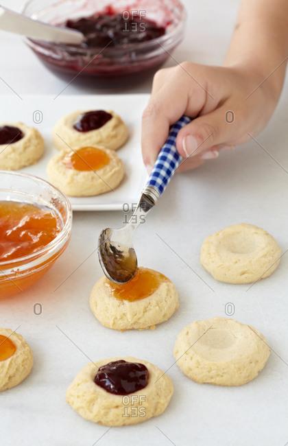 Preparing thumbprint cookies with various jam types at home