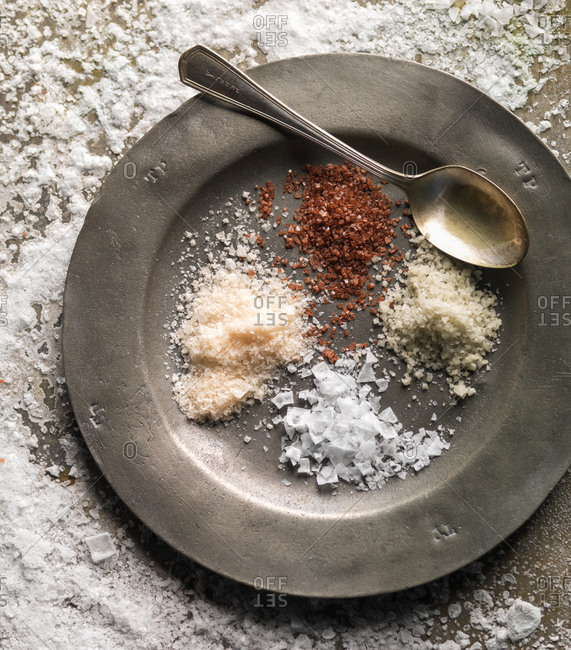 Piles of different kind of salts on pewter plate.