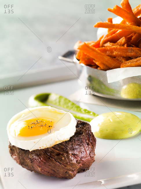 Steak with fried egg and carrot chips