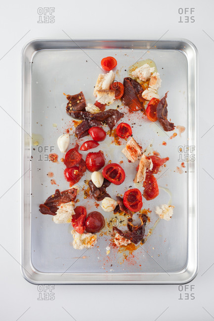 Messy composition with fresh and dried tomatoes, bell pepper, garlic cloves, bread and oil spread on cutting board