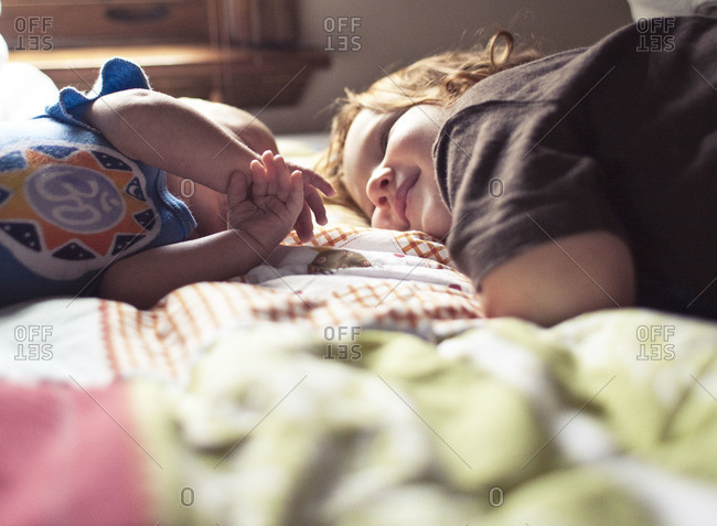 Two kids staring at each other on bed smiling