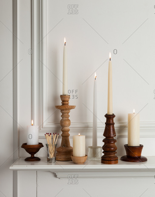Many candles on top of a mantle