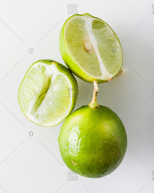 Whole and halved squeezed key limes isolated on a white background