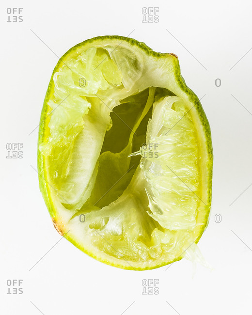 Halved squeezed key lime isolated on a white background