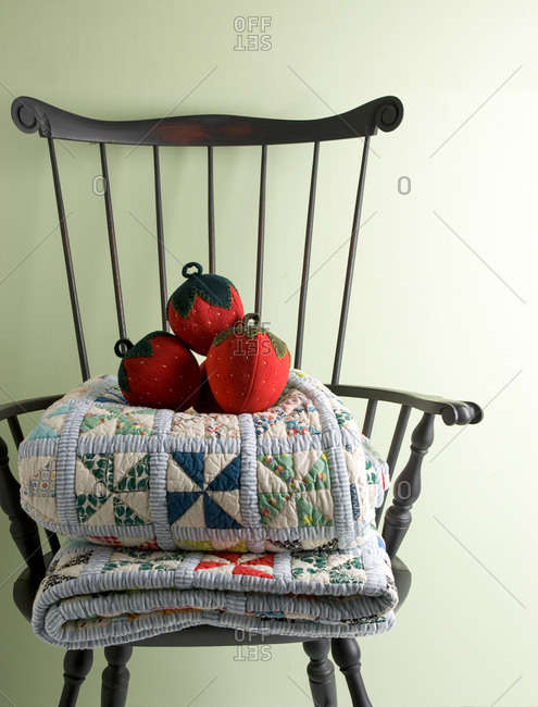 A vintage chair with folded quilts