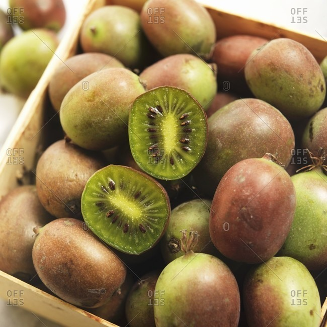 Crate of Fresh Kiwi Berries with One Halved