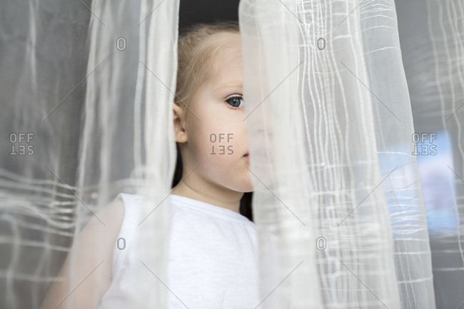 Girl peeking between translucent curtains