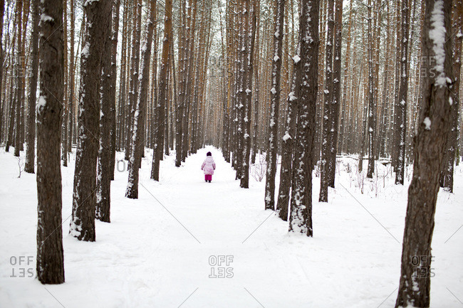A young girl walking down a snow packed path in the forest