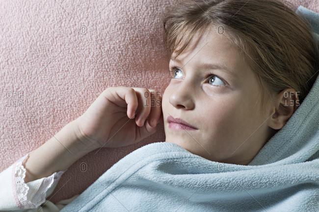 Daydreaming girl under blanket