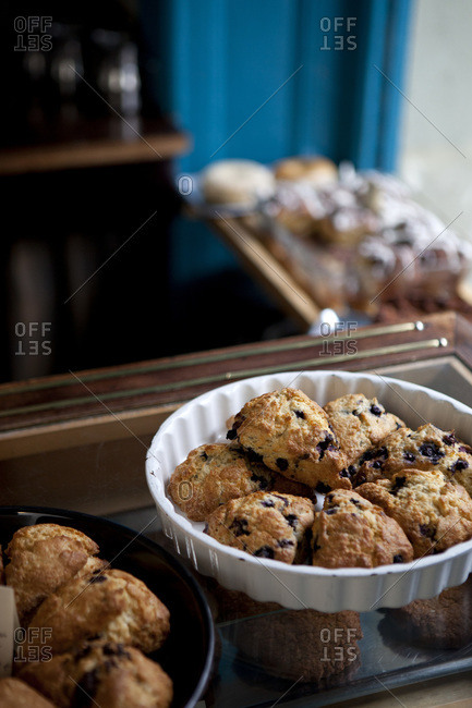 A variety of scones for sale on display in a coffee shop