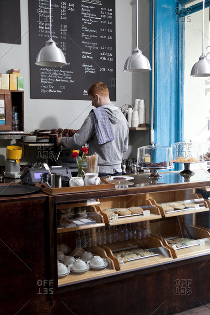 A barista working at an espresso maker in a cafe, rear view