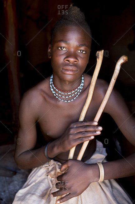 Portrait of young Himba man holding sticks