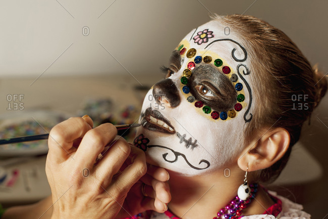 Girl having face painted for Dia de los Muertos