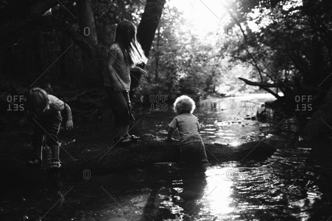 A group of children play near a riverbed together