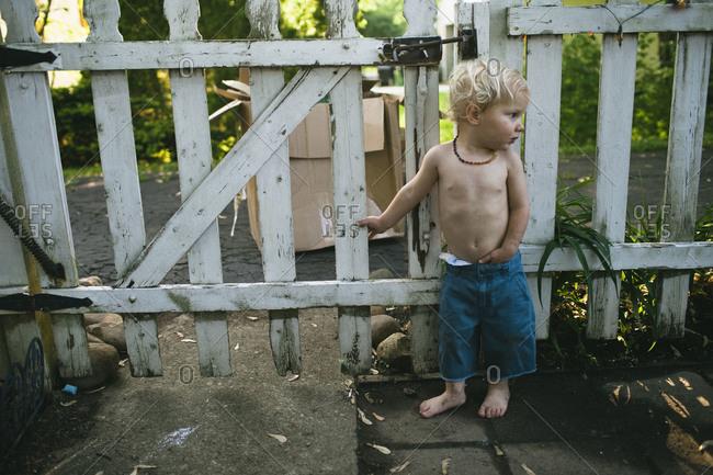 A little boy waits at a fence