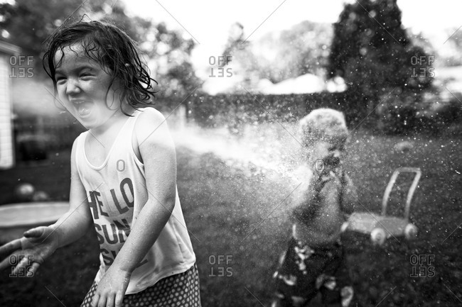 Two children enjoy playing in a stream of water