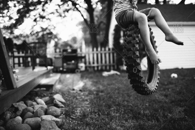 A child rides a tire swing