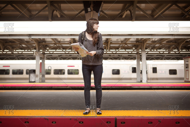 Young woman waiting for a train at the station with map in hand