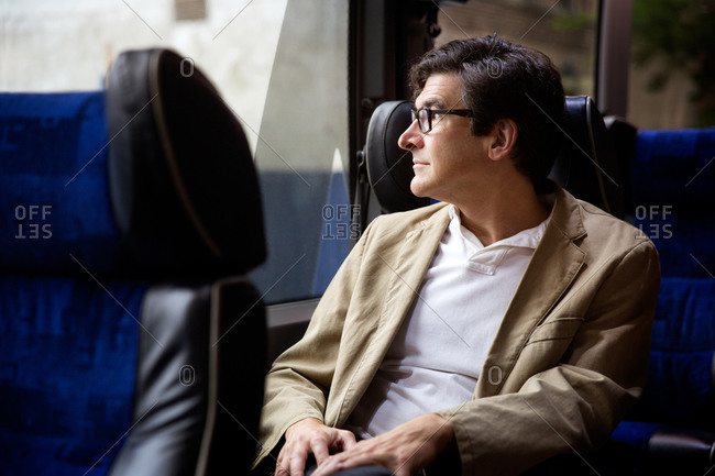 Man sitting on a bus and looking through window