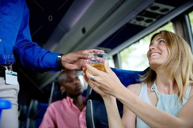 Conductor giving drink to passenger on a bus