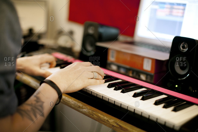 Musician is playing melody on keyboards in studio.