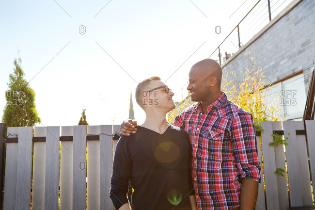 Happy gay couple standing in front of fence