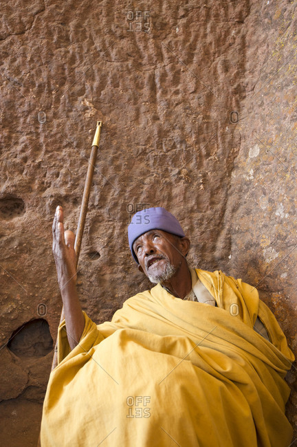 Ethiopian man praying by the wall of a rock-hewn church in Lalibela, Ethiopia