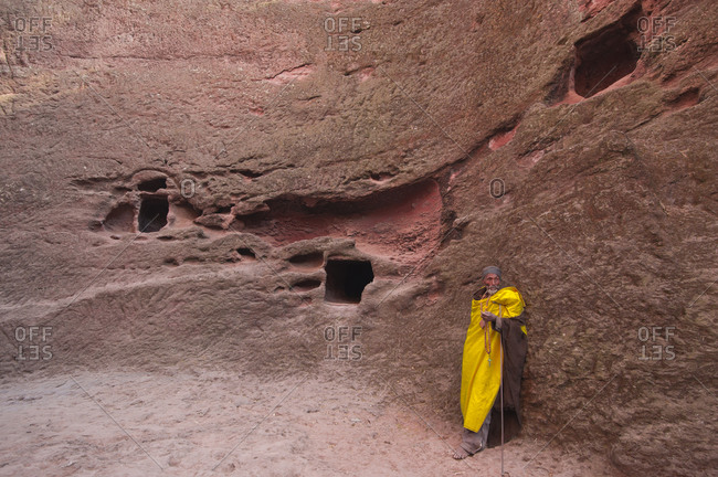 Ethiopian man standing by the wall of a rock-hewn church in Lalibela, Ethiopia