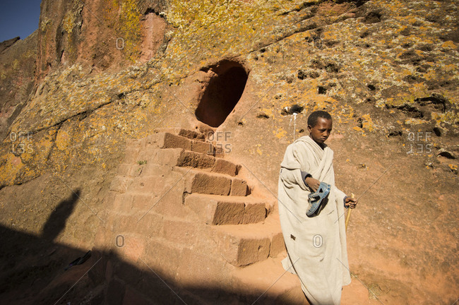 Ethiopian boy climbing down rock-hewn steps in Lalibela, Ethiopia