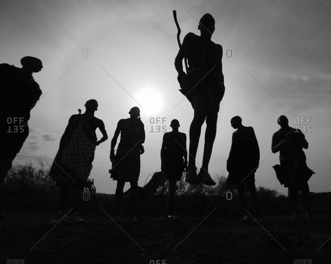 Silhouette of Maasai warriors jumping in Maasai Mara National Reserve, Kenya