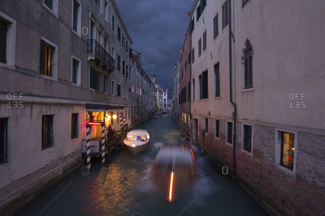 Motorboat speeding along a canal in Venice, Italy