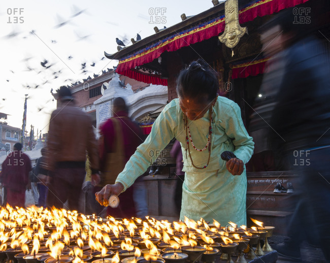 Elderly woman lighting incense butter candles in Kathmandu, Nepal