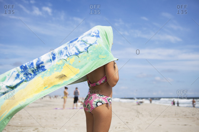 Side-view of young girl sheltering from sun with towel on beach.