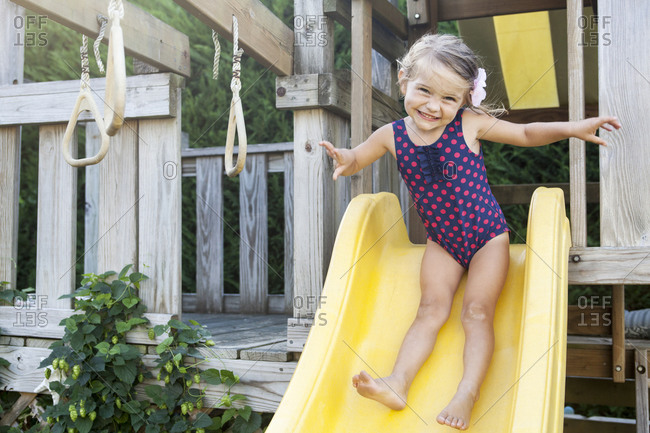 Little girl sliding on yellow children's chute