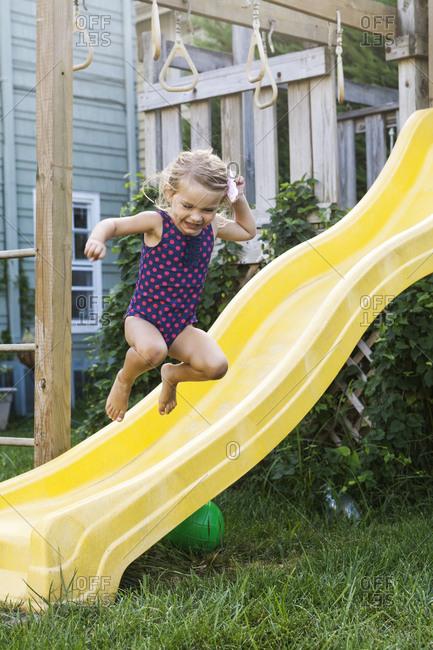 Little Caucasian girl jumping from children's chute.