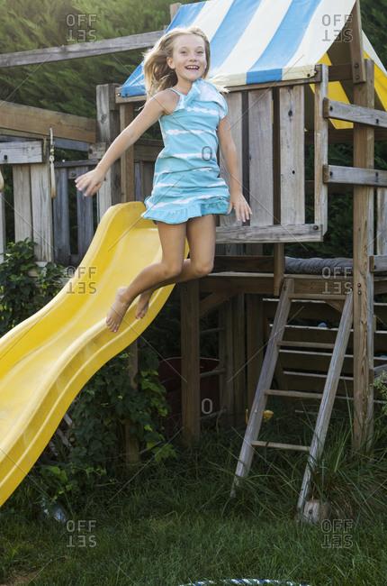 Caucasian girl jumping from children's chute.