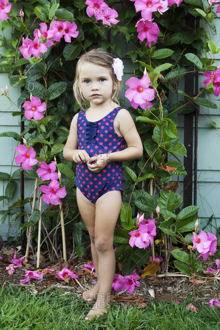 Cute blonde little girl posing in front of pink flowers.