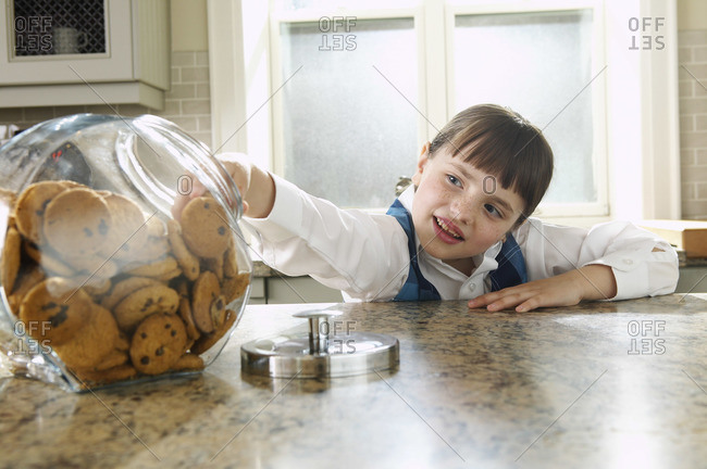 Girl taking cookie from jar