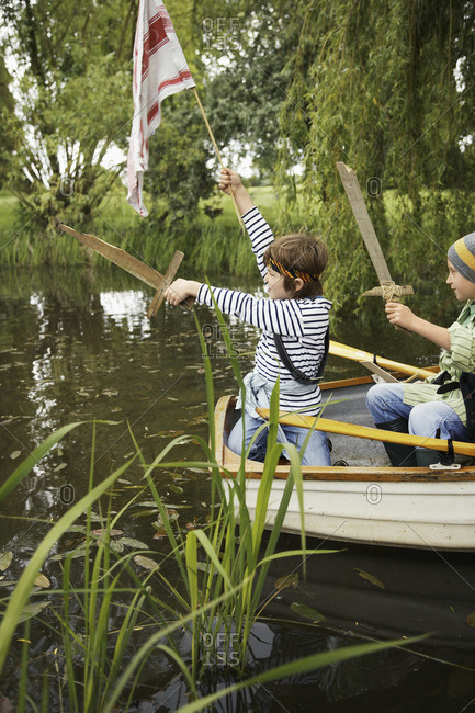 Boys in rowboat pretending to be pirates
