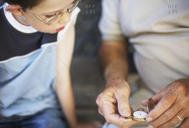 Boy looking at man's pocket watch
