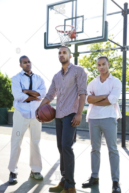 Three african american men in business suit standing on basketball court