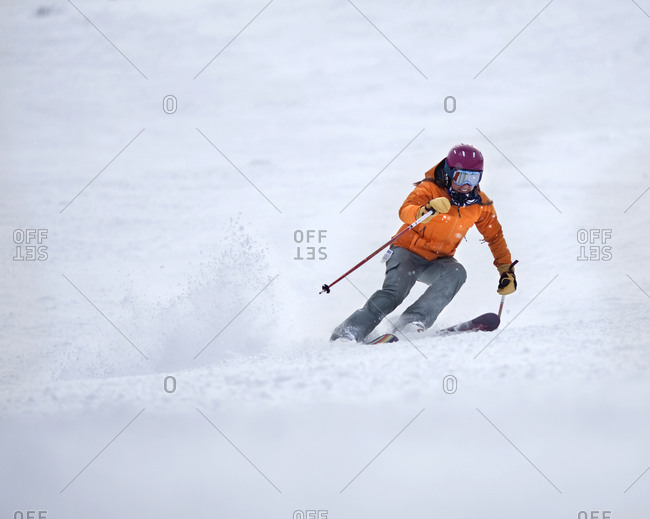A female skier smiles while skiing fast down a groomed trail.