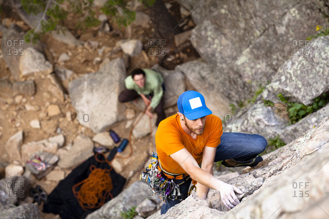 A male climber wearing an orange shirt, blue jeans, and a bright blue hat climbs North Face Center (5.7+) on Cob Rock in Boulder Canyon Colorado.