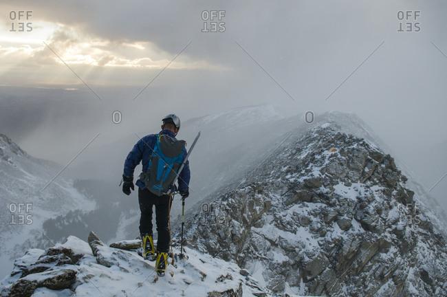 A man climbing Little Bear Peak above Como Lake in the Rio Grande National Forest, Alamosa, Colorado.